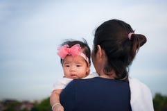 Conceito da ligação do dia da mãe com cuidados recém-nascidos do bebê A mãe está guardando o bebê recém-nascido com a faixa do ro Imagem de Stock