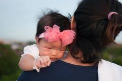Conceito da ligação do dia da mãe com cuidados recém-nascidos do bebê A mãe está guardando o bebê recém-nascido com a faixa do ro Foto de Stock