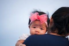 Conceito da ligação do dia da mãe com cuidados recém-nascidos do bebê A mãe está guardando o bebê recém-nascido com a faixa do ro Fotos de Stock