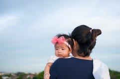 Conceito da ligação do dia da mãe com cuidados recém-nascidos do bebê A mãe está guardando o bebê recém-nascido com a faixa do ro Foto de Stock Royalty Free
