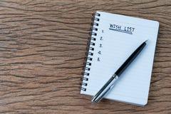 Conceito da lista de objetivos pretendidos, pena na almofada de nota do Livro Branco com escrito à mão foto de stock