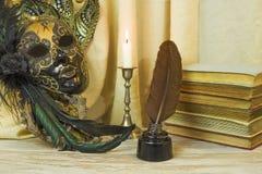 Conceito da literatura, vela em um castiçal perto de uma máscara Venetian Imagens de Stock Royalty Free