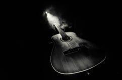Conceito da música Guitarra acústica em um fundo escuro sob o feixe de luz com fumo com espaço da cópia Cordas da guitarra, fim imagens de stock