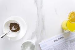 Conceito da manhã do negócio no escritório Xícara de café, vidro do wate, suco de laranja e jornal fresco copie o espaço para seu foto de stock royalty free