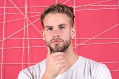Conceito da masculinidade Homem com a cerda na cara pensativa, fundo cor-de-rosa E fotografia de stock
