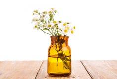 Conceito da medicina alternativa - garrafa com a camomila em Ta de madeira Imagens de Stock Royalty Free
