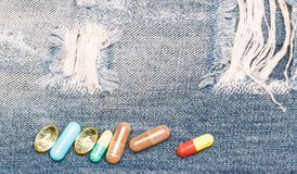 Conceito da medicina e do tratamento Drogas no fundo da sarja de Nimes Jogo de comprimidos coloridos Medicinas de mistura Tratame imagem de stock royalty free