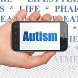 Conceito da medicina: Mão que guarda Smartphone com autismo na exposição Imagem de Stock Royalty Free