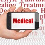 Conceito da medicina: Mão que guarda Smartphone com o médico na exposição Fotos de Stock