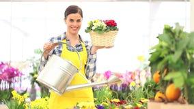 Conceito da mola, florista de sorriso da mulher com cesta das flores e lata molhando vídeos de arquivo