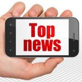 Conceito da notícia: Mão que guarda Smartphone com principais notícias na exposição Foto de Stock