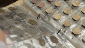Conceito da numismática Coleção das moedas dos países diferentes no álbum vídeos de arquivo