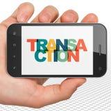 Conceito da operação bancária: Mão que guarda Smartphone com transação na exposição Fotos de Stock