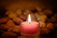 Conceito da oração e da esperança Luz cor-de-rosa retro da vela e pedra velha w fotos de stock