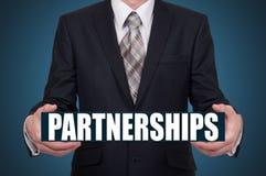 Conceito da parceria e dos trabalhos de equipa Homem de negócios que guarda uma palavra virtual Imagens de Stock