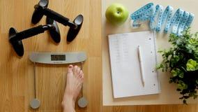 Conceito da perda da aptidão e de peso, escala e caderno em uma tabela de madeira filme