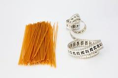 Espaguetes e fita de medição Imagens de Stock