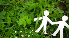 Conceito da pessoa e do ambiente Figuras humanas feitas do papel na grama Utilização horizontal da câmera do movimento lento do p vídeos de arquivo
