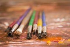 Conceito da pintura, escovas em um fundo das pinturas Fotografia de Stock Royalty Free