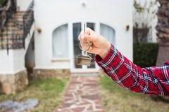 Conceito da posse, da propriedade e do inquilino - chave à disposição para a casa nova e bens imobiliários imagem de stock