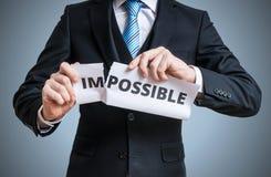 Conceito da possibilidade O homem está rasgando o papel com palavra impossível fotografia de stock