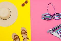 Conceito da praia Chapéu do ` s das mulheres, sandálias, roupa de banho, óculos de sol Amarelo com fundo cor-de-rosa, vista super Fotos de Stock Royalty Free