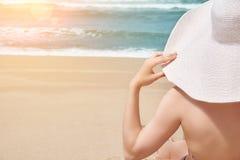 Conceito da praia do verão Mulher no chapéu grande na praia idílico A praia do oceano relaxa, viaja Fotografia de Stock Royalty Free