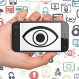 Conceito da privacidade: Mão que guarda Smartphone com o olho na exposição Foto de Stock Royalty Free