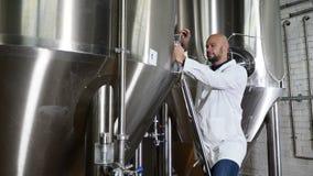 Conceito da produção da cerveja Escrita atenta do trabalhador da manutenção na prancheta na cervejaria O empregado da cervejaria filme