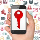 Conceito da proteção: Mão que guarda Smartphone com chave na exposição Fotografia de Stock