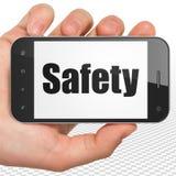 Conceito da proteção: Mão que guarda Smartphone com segurança na exposição Imagens de Stock