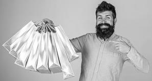 Conceito da recomendação Compra do indivíduo e apontar em sacos O homem com barba e bigode leva o grupo dos sacos de compras imagem de stock royalty free