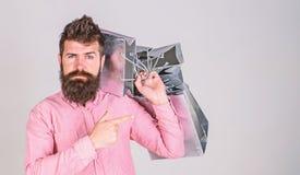 Conceito da recomendação A compra do indivíduo em vendas tempera, apontando em sacos O homem com barba e bigode leva o grupo de fotografia de stock royalty free