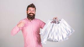 Conceito da recomendação O moderno na cara de sorriso recomenda comprar A compra do indivíduo em vendas tempera, apontando em sac imagens de stock