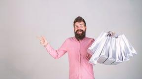 Conceito da recomendação O moderno na cara de sorriso recomenda comprar O homem com barba e bigode leva o grupo da compra imagens de stock