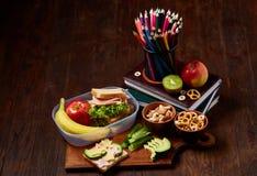 Conceito da ruptura do almoço escolar com fontes saudáveis da lancheira e de escola na mesa de madeira, foco seletivo imagem de stock royalty free