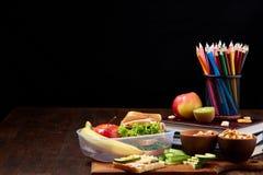 Conceito da ruptura do almoço escolar com fontes saudáveis da lancheira e de escola na mesa de madeira, foco seletivo imagens de stock