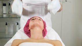 Conceito da saúde e da beleza O esteticista remove a máscara cosmética facial da cara fêmea do cliente Feche acima de vestir das  video estoque