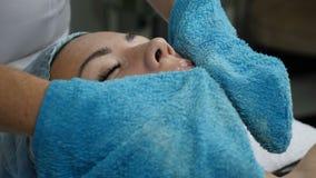 Conceito da saúde e da beleza O esteticista remove a máscara cosmética facial da cara fêmea do cliente s Feche acima de vestir da filme
