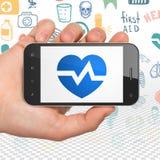 Conceito da saúde: Mão que guarda Smartphone com coração na exposição Foto de Stock