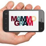 Conceito da saúde: Mão que guarda Smartphone com mamograma na exposição Imagem de Stock Royalty Free