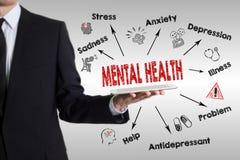 Conceito da saúde mental Carta com palavras-chaves e ícones Homem novo que guarda um tablet pc imagem de stock