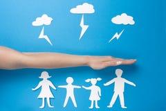 Conceito da segurança da família Seguro de vida e saúde da família Mãos de papel da posse dos povos do origâmi fotografia de stock royalty free