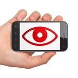 Conceito da segurança: Mão que guarda Smartphone com o olho na exposição Fotos de Stock Royalty Free