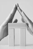 Conceito da segurança ou do seguro com as mãos que protegem a construção feita dos blocos de madeira Imagem de Stock Royalty Free