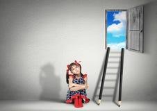 Conceito da solução, menina da criança que sonha perto das escadas dos lápis fotografia de stock