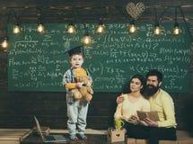 Conceito da sustentação A criança guarda o urso e a execução de peluche Menino que apresenta seu conhecimento à mamã e ao paizinh fotografia de stock