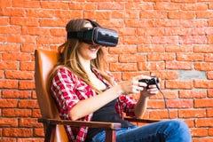 Conceito da tecnologia, da realidade virtual, do entretenimento e dos povos - mulher com os auriculares do vr que jogam o jogo Imagens de Stock