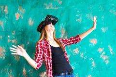Conceito da tecnologia, do entretenimento e dos povos - jovem mulher feliz com os auriculares da realidade virtual ou os vidros 3 foto de stock royalty free
