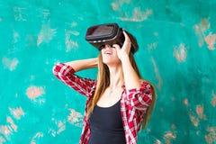 Conceito da tecnologia, do entretenimento e dos povos - jovem mulher feliz com os auriculares da realidade virtual ou os vidros 3 foto de stock